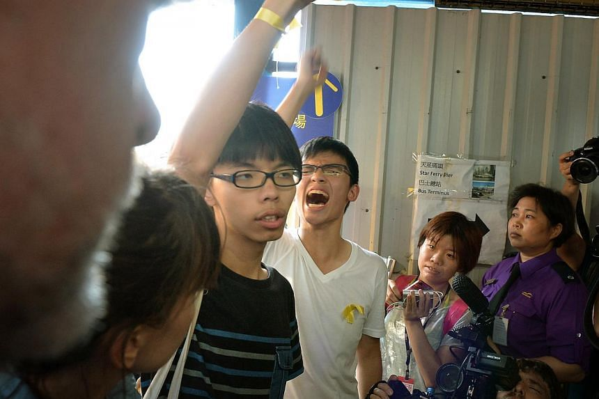 Student activist, Joshua Wong (centre, in black) exiting the Hong Kong Convention and Exhibition Centre in Wan Chai after he attended the flag-raising ceremony and National Day reception at HKCEC to celebrate the 65th anniversary of the founding of t