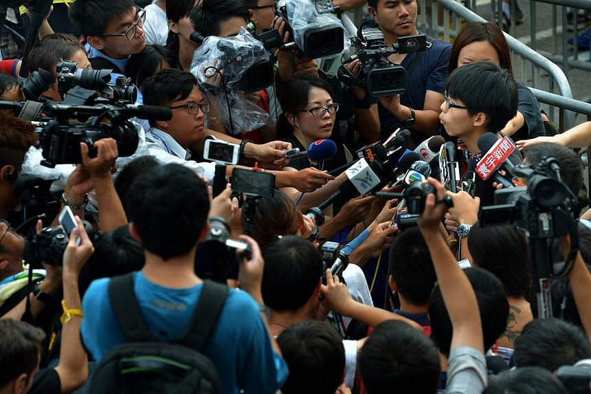 Student activist, Joshua Wong speaking to reporters outside the Hong Kong Convention and Exhibition Centre in Wan Chai after he had attended the flag-raising ceremony and National Day reception. -- ST PHOTO: KUA CHEE SIONG