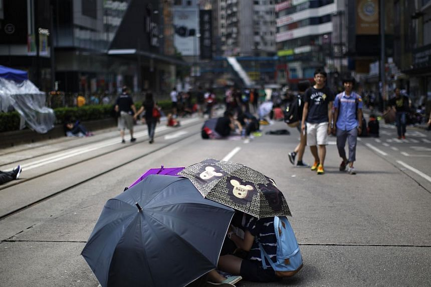 Protesters hiding from the sun as they block an area near the government headquarters building in Hong Kong on Oct 1, 2014. -- PHOTO: REUTERS