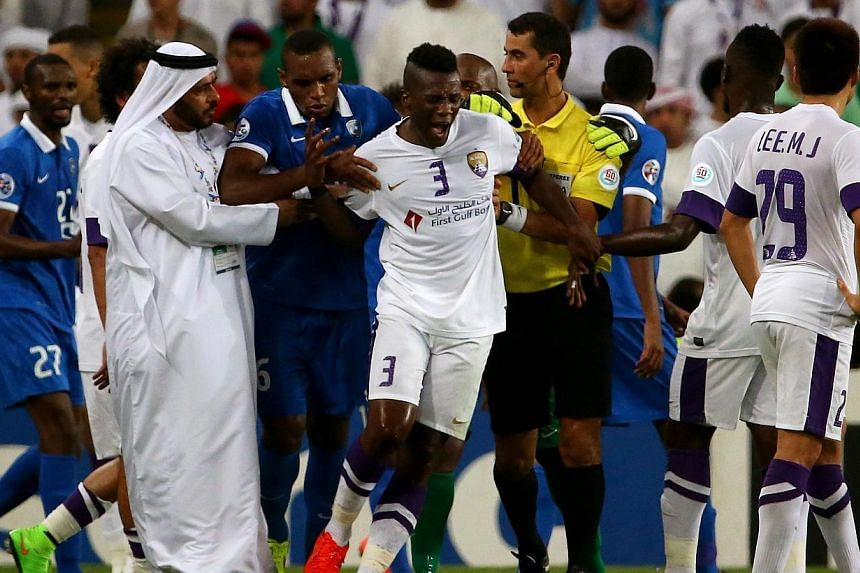 Players, officials and staff try to calm UAE's al-Ain forward Asamoah Gyan (centre, #3) following altercation between Al-Ain and Al-Hilal players during their AFC Champions League semi-final football match on Sept 30, 2014 at Hazza Bin Zayed Stadium