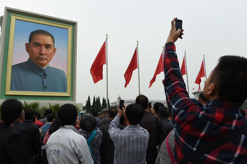 A man takes photos of a portrait of Sun Yat-sen in Beijing's Tiananmen Square on China's National Day, Oct 1, 2014.Fearful of comparisons to the 1989 Tiananmen Square crackdown, Beijing has launched a dual effort to suppress news of swelling pr