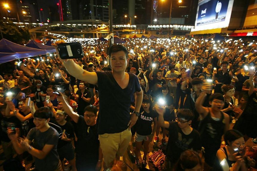 Protesters turn on their mobile phone flashlights as they block an area outside the government headquarters building in Hong Kong Oct 1, 2014. -- PHOTO: REUTERS