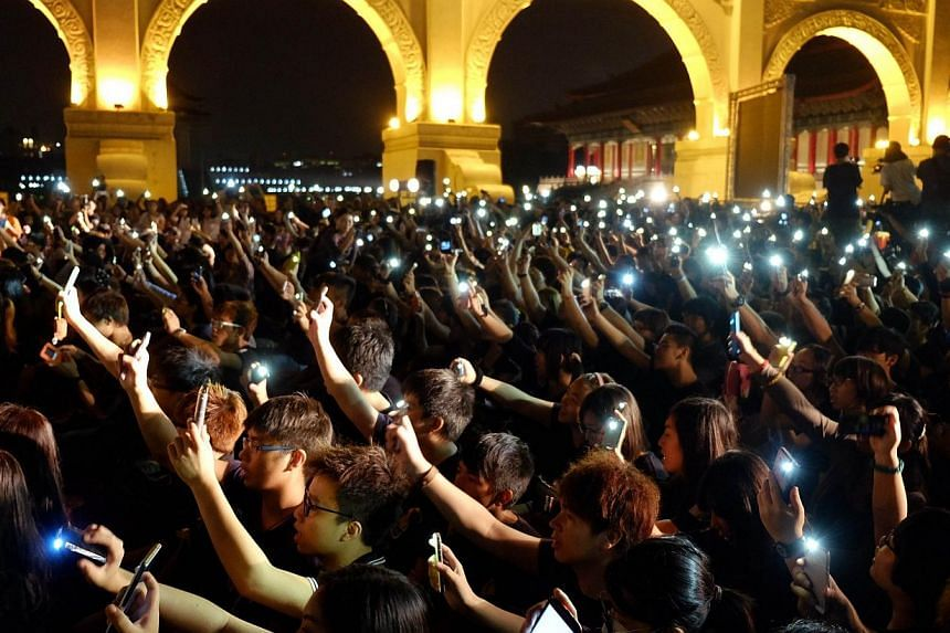 Students from Taiwan and Hong Kong raise their mobile phones in front of the Freedom square during a gathering in support of Hong Kong's pro-democracy protestors, in Taipei on Oct 1, 2014. -- PHOTO: AFP