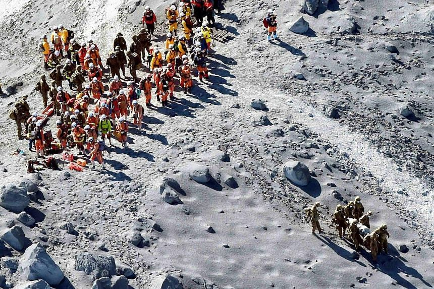 Japan Self-Defense Force (JSDF) soldiers and firefighters conduct rescue operations near the peak of Mt. Ontake, which straddles Nagano and Gifu prefectures, central Japan on Oct 1, 2014, in this photo taken and released by Kyodo.Seven more bod