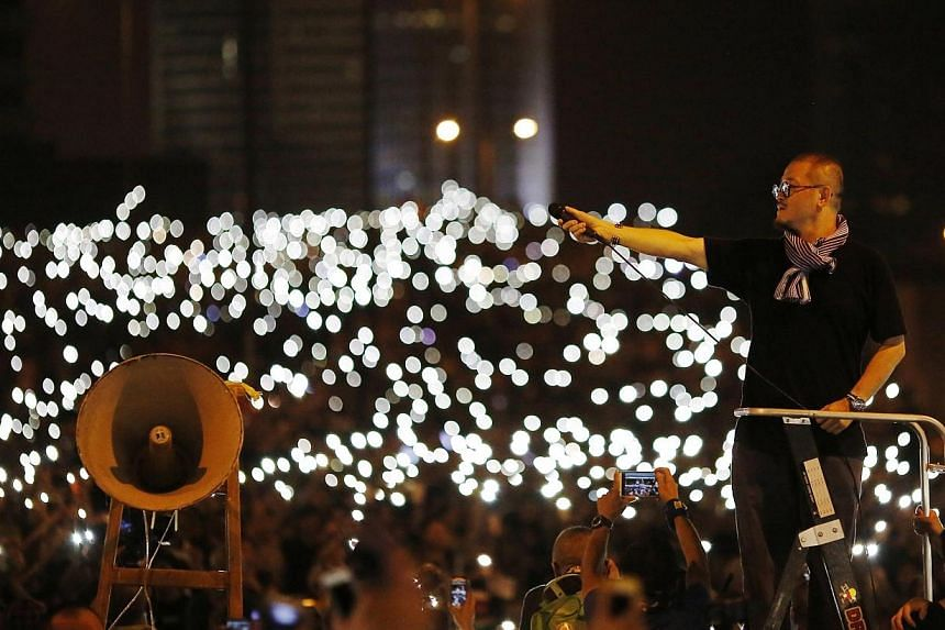 A man holds a microphone as protesters turn on their mobile phone flashlights outside the government headquarters building in Hong Kong Oct 1, 2014. -- PHOTO: REUTERS