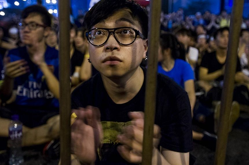 A protestor listens to a pro-democracy speech in the Admiralty district of Hong Kong on Oct 1, 2014. -- PHOTO: AFP