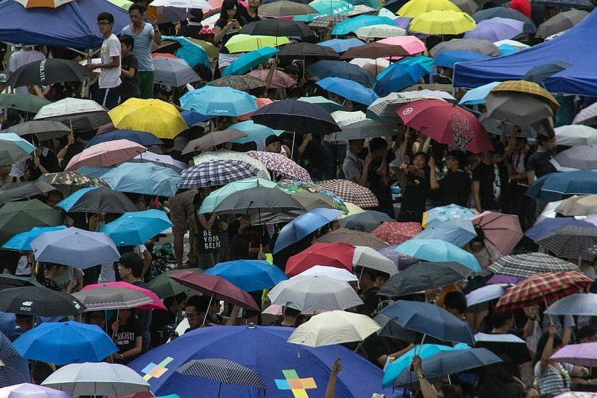 "Pro-democracy protesters raise their umbrellas on cue as part of the demonstrations currently blocking central Hong Kong that have been dubbed the ""umbrella revolution"", on Oct 1, 2014. -- PHOTO: AFP"