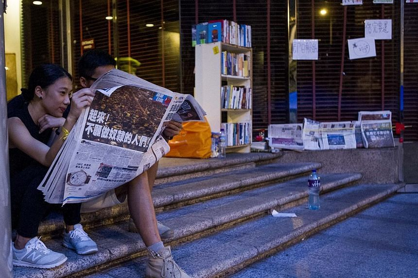 Protesters read a newspaper close to an improvised library in the Admiralty district of Hong Kong on Oct 1, 2014, during a gathering of pro-democracy protestors. -- PHOTO: AFP