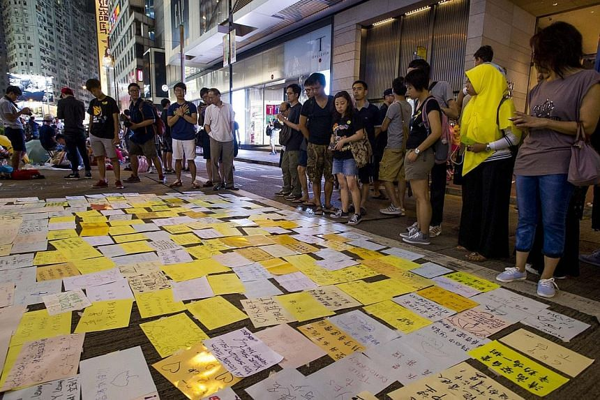 Notes written by pro-democary supporters are displayed on the ground in the Causeway Bay district of Hong Kong on Oct 1, 2014. -- PHOTO: AFP