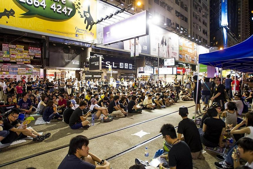 Pro-democary protesters gather in the Causeway Bay district of Hong Kong on Oct 1, 2014. -- PHOTO: AFP