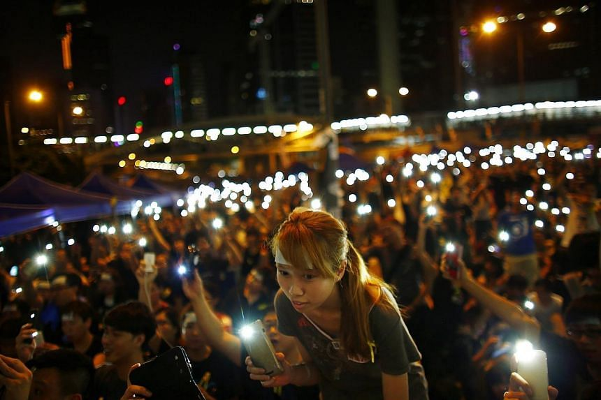 Protesters turn on their mobile phone flashlights as they block an area outside the government headquarters building in Hong Kong on Oct 1, 2014. -- PHOTO: REUTERS