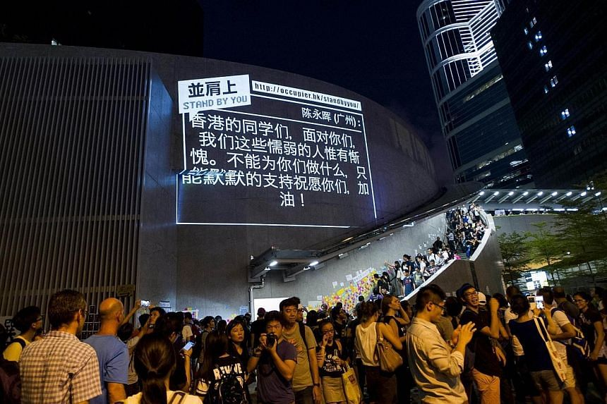 A message of support from the pro-democracy movement is projected onto the government offices in the Admiralty district of Hong Kong on Oct 1, 2014. -- PHOTO: AFP