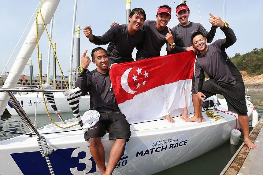 (From left) Singapore's Justin Wong, skipper Maximilian Soh, Russell Kan, Christopher Lim and Andrew Paul Chan after bagging Singapore's third sailing gold medal at the Incheon Asian Games on Oct 1, 2014. -- ST PHOTO: NEO XIAOBIN