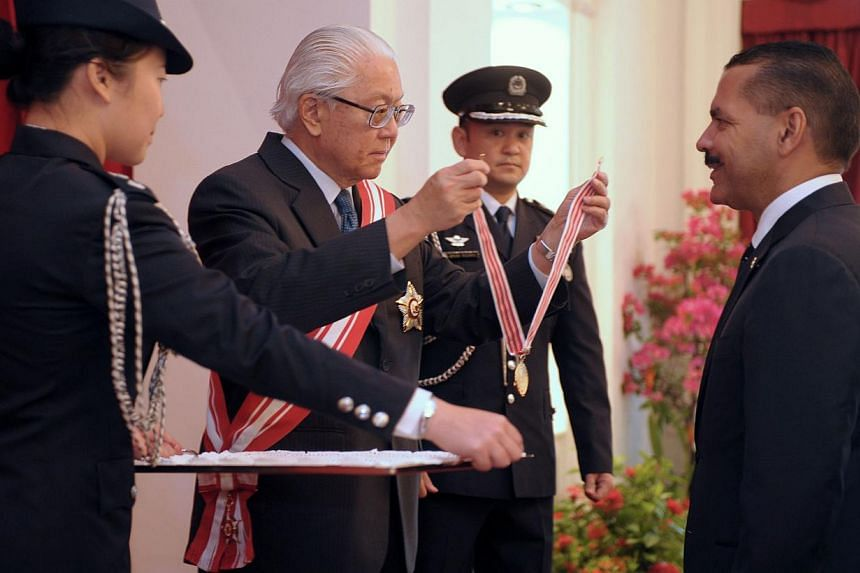 Singapore President Tony Tan Keng Yam presents a distinguished service order medal to Interpol secretary-general Ronald Noble at the Istana on Oct 1, 2014. Mr Noble played an important role in fostering close ties between Singapore and Interpol,