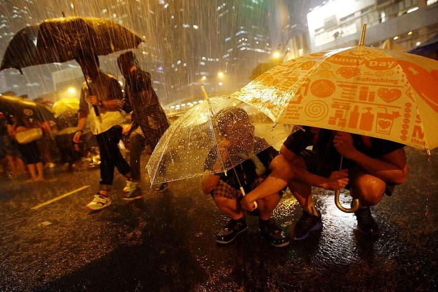 Protesters taking shelter from the rain under umbrellas as they block the main street to the financial Central district outside of the government headquarters in Hong Kong onSept30, 2014. --PHOTO: REUTERS
