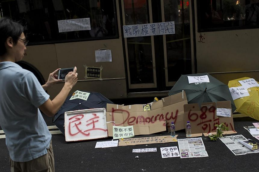 Umbrellas and signs placed along a main street at Mongkok shopping district on Sept30,2014. -- PHOTO: REUTERS