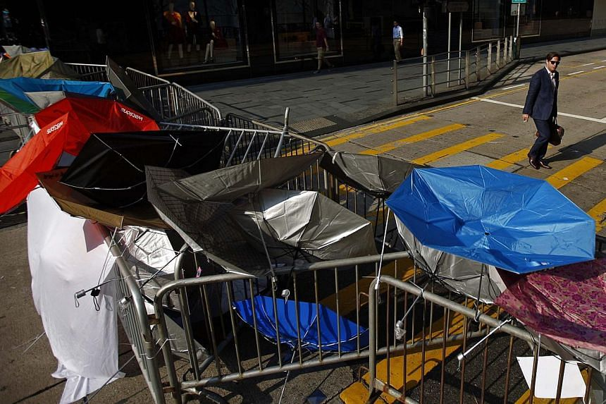 A barricade of metal fence and umbrellas on a street at the central financial district, near the government headquarters on Sept30, 2014.-- PHOTO: REUTERS