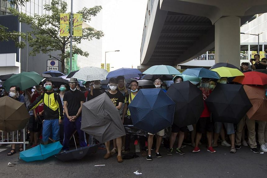 Protesters carrying umbrellas in case they are pepper-sprayed during a confrontation with the police on Sept27, 2014.-- PHOTO: REUTERS