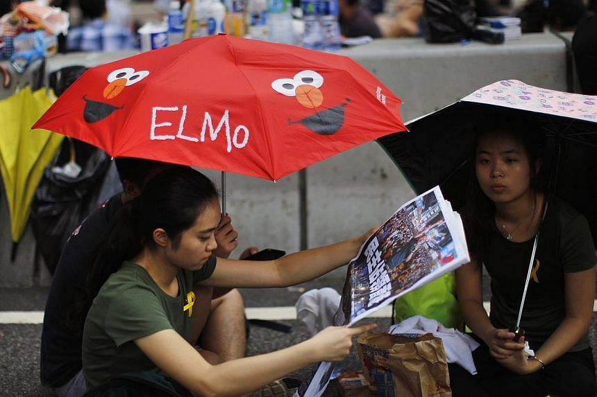 Protesters sitting under umbrellas as they block the main street to the financial Central district outside the government headquarters in Hong Kong on Sept30, 2014. -- PHOTO: REUTERS