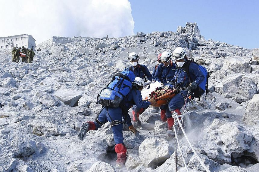 Firefighters carry a hiker during rescue operations near the peak of Mount Ontake in central Japan in this handout photograph released by the Tokyo Fire Department and taken on Sept 28, 2014. -- PHOTO: REUTERS