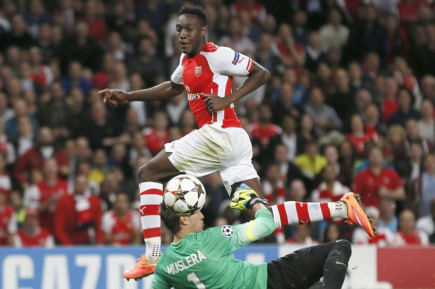 Arsenal's Danny Welbeck (top) scores a goal past Galatasaray's goalkeeper Fernando Muslera during their Champions League match at the Emirates Stadium in London on Oct 1, 2014. -- PHOTO: REUTERS