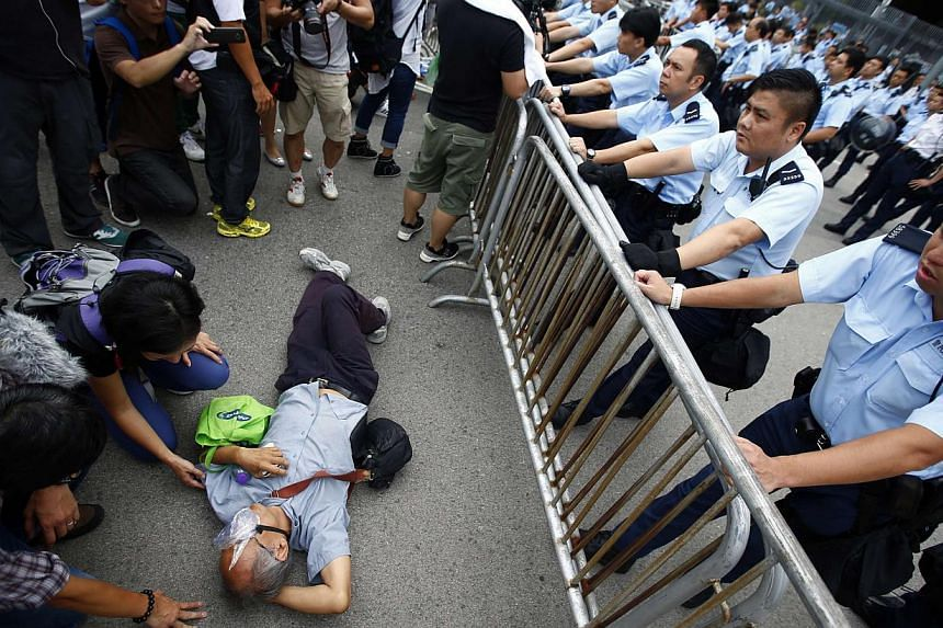 Police officers try to remove a protester from the entrance to Hong Kong's Chief Executive Leung Chun Ying offices next to the government headquarters building in Hong Kong on Oct 2, 2014. -- PHOTO: REUTERS