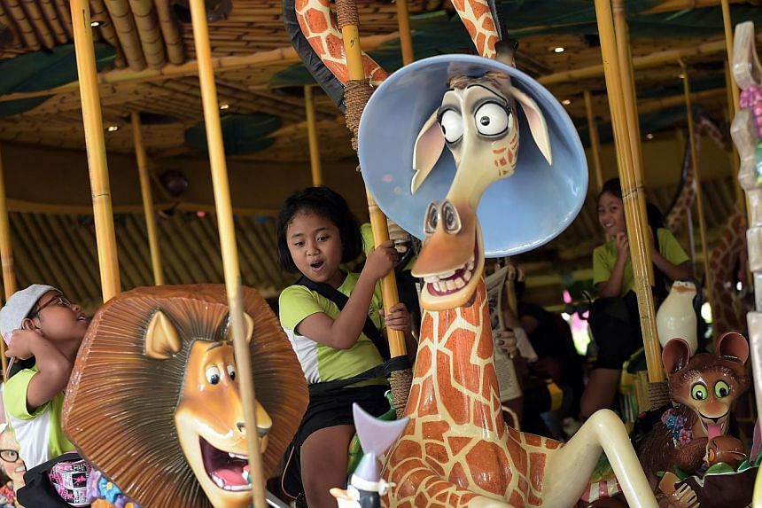 Aqilah Fadil (centre), 10 of Griffiths Primary School reacts as the ride she's on 'King Julien's Beach Party-Go-Round' sets off at Universal studios during Children for Children 2014.-- ST PHOTO: JOSEPH NAIR