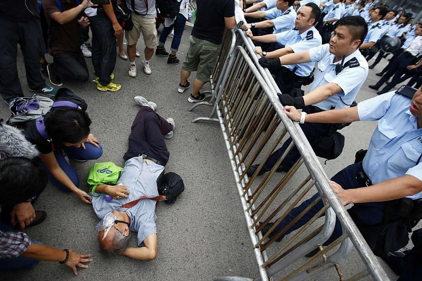 Police officers try to remove a protester from the entrance to Hong Kong's Chief Executive Leung Chun-ying offices next to the government headquarters building in Hong Kong, Oct 2, 2014. -- PHOTO: REUTERS