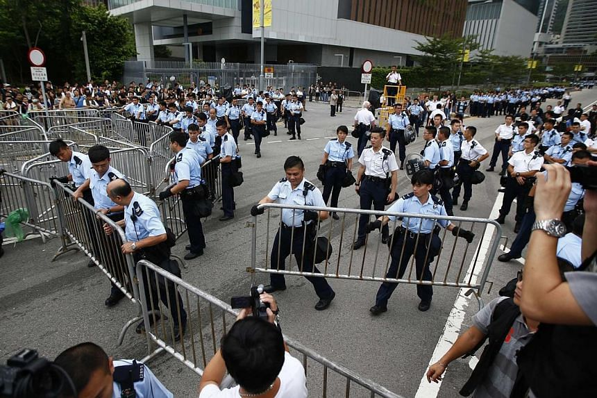 Police officers install metal fences near the entrance to the offices of Hong Kong's Chief Executive Leung Chun-ying in Hong Kong, Oct 2, 2014. -- PHOTO: REUTERS
