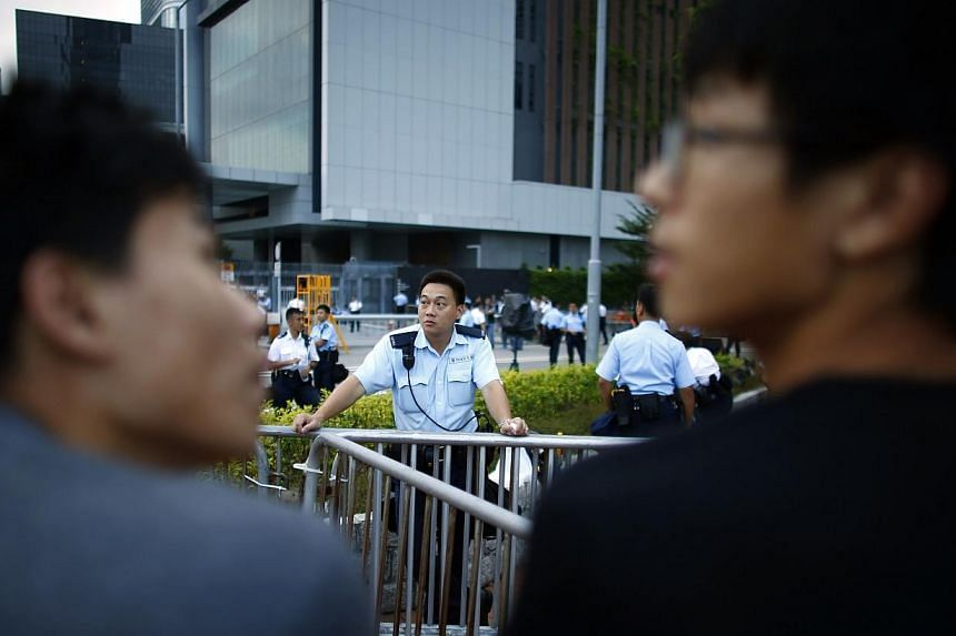 A police officer stands next to metal fences as protesters block the entrance of Hong Kong Chief Executive Leung Chun-ying's offices, next to the government headquarters building in Hong Kong, Oct 2, 2014. -- PHOTO: REUTERS