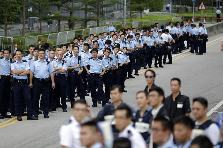 Police officers gather as protesters block the entrance to Hong Kong's Chief Executive Leung Chun-ying offices in Hong Kong, Oct 2, 2014. -- PHOTO: REUTERS