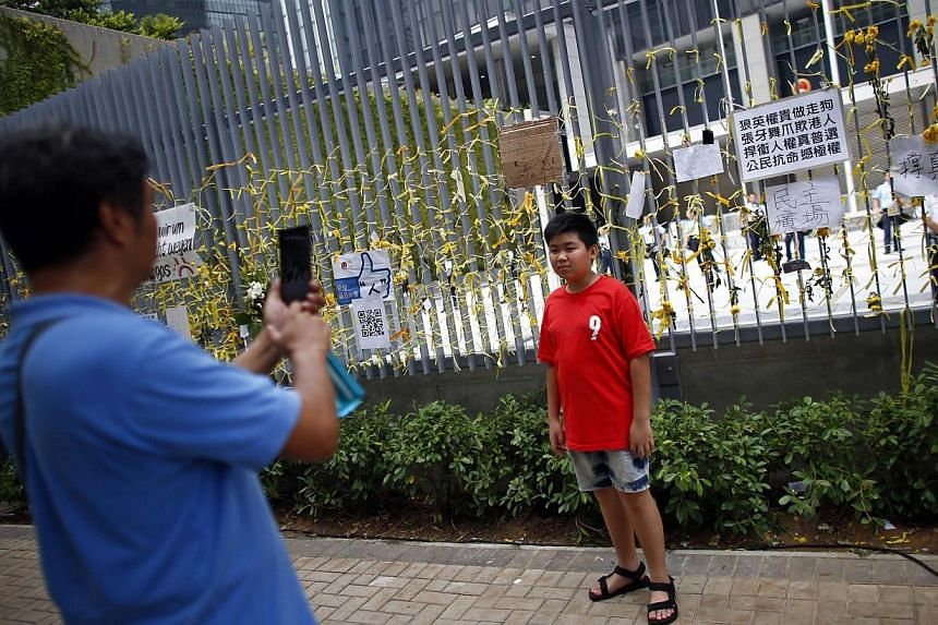 A man take pictures of his son, standing near a fence adorned with yellow ribbons and messages in support of the pro-democracy demonstrations, in front of the government headquarters as protesters block the surrounding areas in Hong Kong on Oct 2, 20