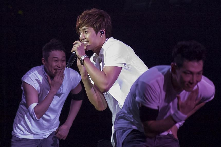 Korean pop star Kim Hyun Joong performing at the Singapore Indoor Stadium on May 4, 2012.All charges except one have been dropped against Kim, who is accused of assaulting his ex-girlfriend, the local police said on Monday. -- PHOTO: ST FILE