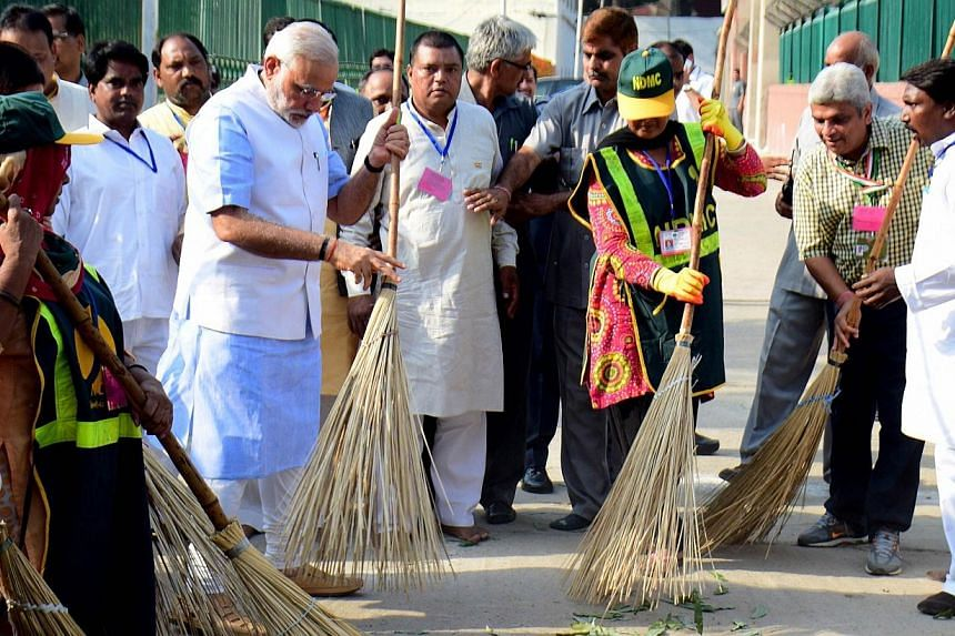 Indian Prime Minister Narendra Modi (left) sweeps a street in a residential colony in New Delhi on Oct 2, 2014. Mr Modi launched the Swachh Bharat Abhiyan, or Clean India Mission, to modernise sanitation within five years on Thursday, Oct 2, 2014, a