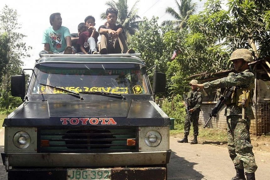 """Soldiers stopping a vehicle at a military checkpoint in Jolo, Sulu, in southern Philippines on Sept 25, 2014.Extremist groups in the restive southern island of Mindanao are seen """"mutating"""" into a """"large, more coordinated, more sophisticated org"""