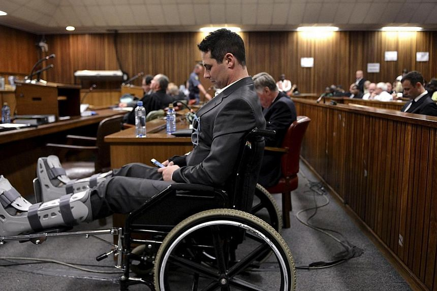 Carl Pistorius, brother of Olympic and Paralympic track star Oscar Pistorius, sits in a wheel chair during Oscar Pistorius' judgment at the North Gauteng High Court in Pretoria, Sept 11, 2014. Police suspected Carl Pistorius of wiping data from