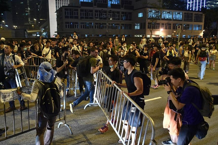 Demonstrators remove barriers after a road was briefly blocked near the government headquarters in Hong Kong on Oct 2, 2014, as pro-democracy protesters remain gathered for the fifth day in a push for free elections of the city's leader. -- PHOTO: AF
