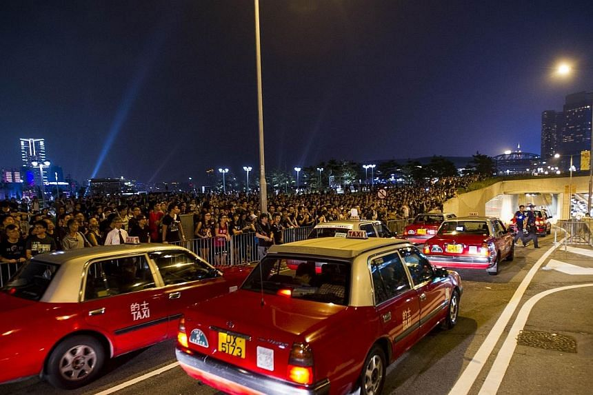 Traffic resumes after protestors briefly managed to block a road near the government offices in Hong Kong on Oct 2, 2014, as pro-democracy protesters remain gathered for the fifth day in a push for free elections of the city's leader. -- PHOTO: AFP