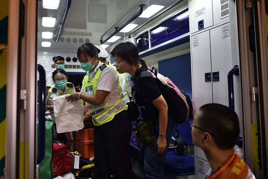 A pro-democracy protestor (2nd right) checks the inside of an ambulance to make sure the ambulance is not being used to carry hidden supplies for the police near the government headquarters in Hong Kong on Oct 2, 2014. -- PHOTO: AFP