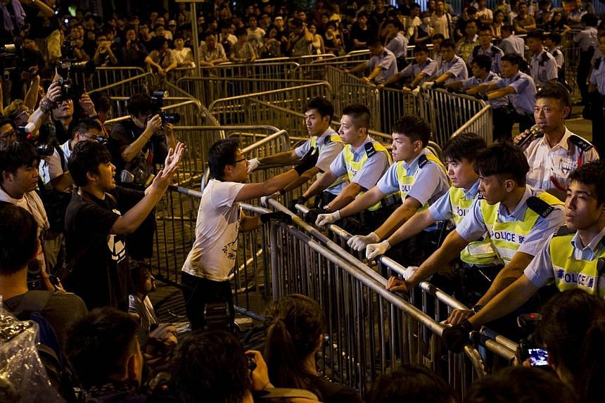 Pro-democracy protesters face policemen as they wait for Hong Kong chief executive outside the Legislative Counsel Office, on Oct 2, 2014, in Hong Kong. Tensions rose in Hong Kong after police were seen unloading boxes of rubber bullets and othe