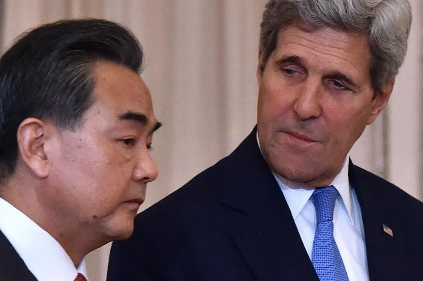 US Secretary of State John Kerry (right) and Chinese Foreign Minister Wang Yi in Washington on Oct 1, 2014. -- PHOTO: AFP