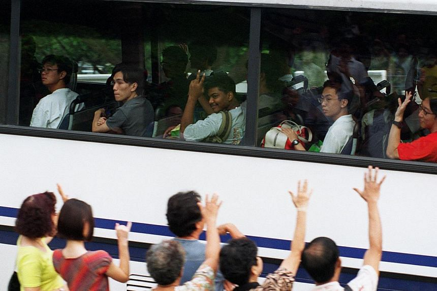 TEARY FAREWELLS: (Above) Family and friends seeing off enlistees as they leave CMPB in an air-conditioned coach in 1997. (Below, right) In 1996, Madam Choo Ah Choon, then 82, giving her grandson, then 18-year-old Daniel Teo Ming Tsin, a hug and a kis