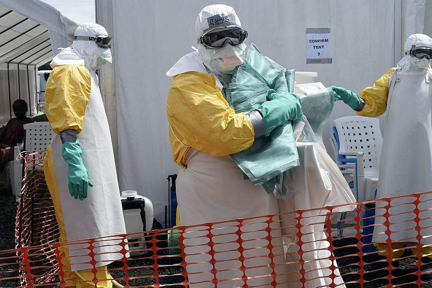 A health worker in protective suit carries equipment on Oct 1, 2014 at MSF's (Doctors Without Borders) Ebola treatment center in Monrovia. -- PHOTO: AFP