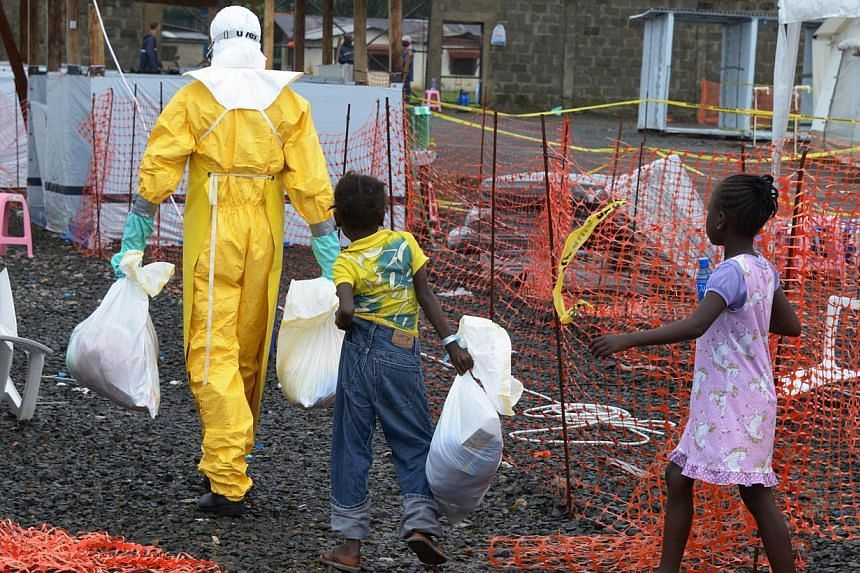 A medical worker wearing a protective suit carries bags followed by Ebola infected children in the high-risk area of the Elwa hospital runned by Medecins Sans Frontieres (Doctors without Borders) in Monrovia, on Sept 7, 2014.  -- PHOTO: AFP