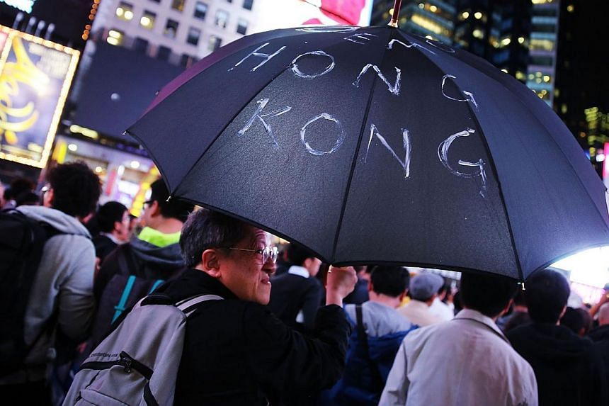 A man holds up an umbrella while demonstrating in New York's Times Square to show solidarity with pro-democracy events in Hong Kong in New York City on Oct 1, 2014. -- PHOTO: AFP