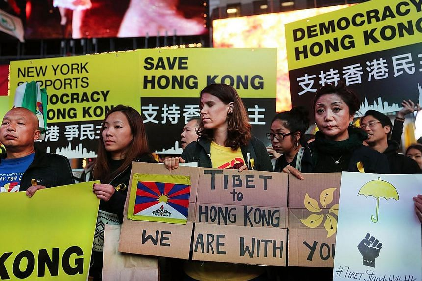 Dozens of protesters hold up umbrellas while demonstrating in New York's Times Square to show solidarity with pro-democracy events in Hong Kong in New York City on Oct 1, 2014. -- PHOTO: AFP