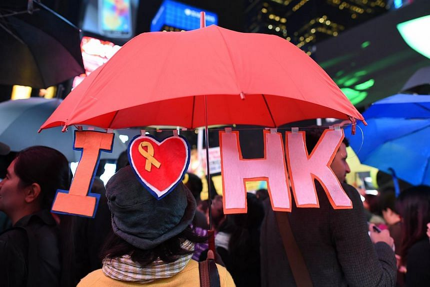 """Hundreds gather in Times Square to rally in support of Hong Kong's """"Umbrella Revolution"""" in New York on Oct 1, 2014. -- PHOTO: AFP"""