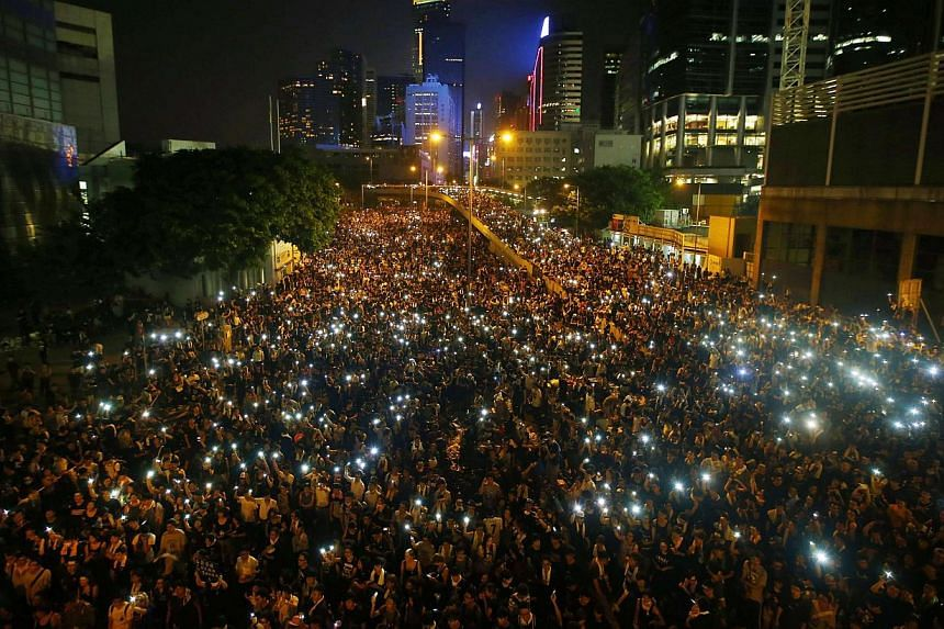 A sea of lights as protesters hold up their mobile phones while blocking the main road to the financial district in Hong Kong on Sept 29, 2014. -- PHOTO: REUTERS
