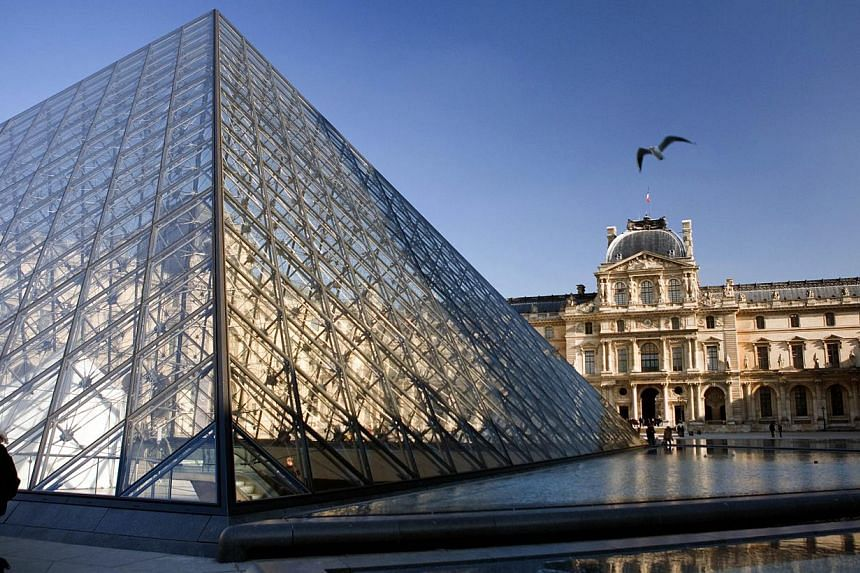 The Louvre Pyramid in Paris. The Louvre, the Palace of Versailles and the Musee d'Orsay - France's top three most visited museums - will soon open seven days a week, the government said on Wednesday. -- PHOTO: AFP