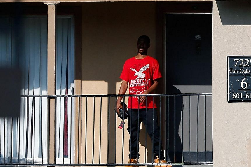 A man stands outside a unit at the Ivy Apartments, where the confirmed Ebola virus patient was staying, on Oct 1, 2014 in Dallas, Texas. -- PHOTO: AFP